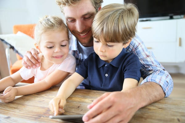 a dad with his arms around his son and daughter showing them something on his phone on a table