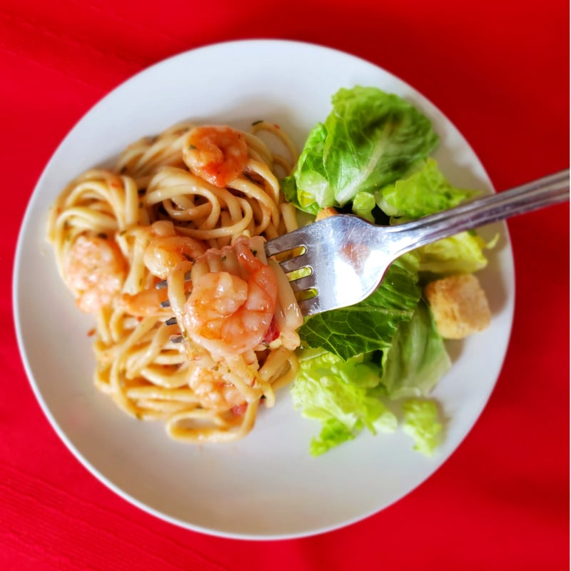 a forkful of food above shrimp, pasta, a salad on a white plate on a red background