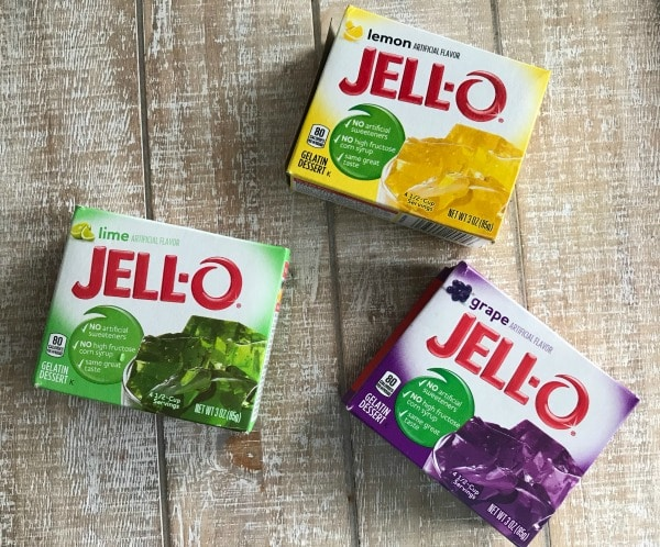 a box of purple, yellow, green jello for Mardi Gras on a wood background