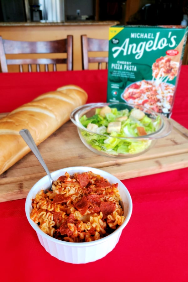 a bowl of pasta with a cutting board, loaf of bread, bowl of salad, and Michael Angelo's box of food on a red tablecloth