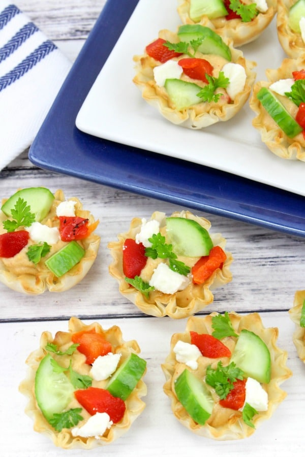 Roasted Red Pepper Hummus Phyllo Cup Appetizers on a table and on white and blue plates