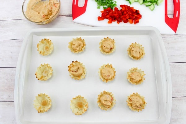 phyllo cups filled with hummus in a white backing dish with hummus and vegetables on a cutting board in the background