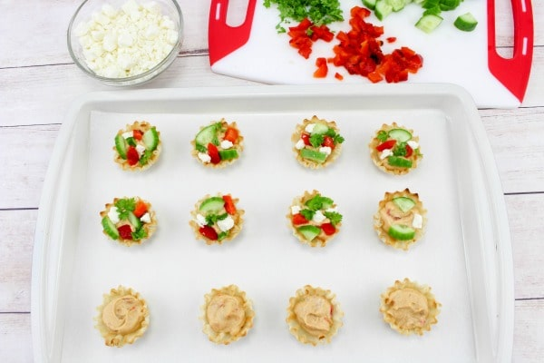 hummus filled phyllo cups in a baking dish, some of them are topped with red pepper, cucumber and parsley with chopped vegetables on a cutting board and a glass bowl of cheese in the background