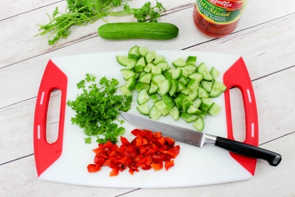 chopped red peppers, parsley and cucumber on a cutting board with a knife, with a cucumber, parsley and jar of red peppers in the background