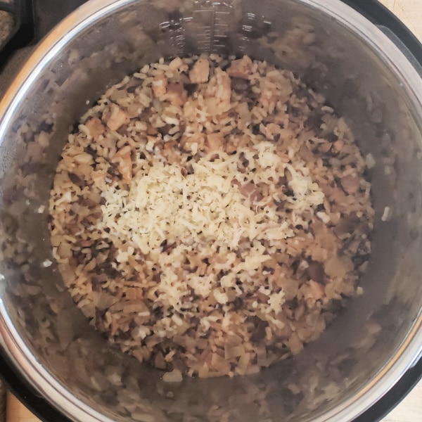 pork, rice, onions in an instant pot topped with cheese