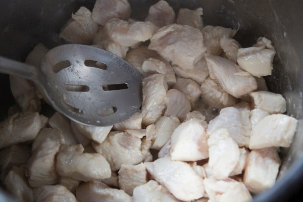 a spoon in an instant pot filled with cooked diced chicken