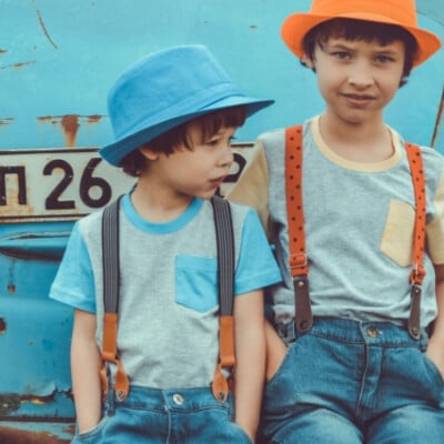 sibling brothers wearing hats leaning against an old blue car