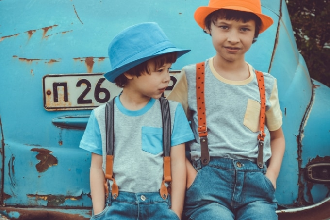 two boys wearing hats sitting on the back bumper of a car
