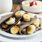 Chocolate Nutella and Banana Crepes on white plate with cup of milk in background