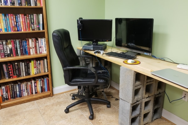 a room with a bookcase, chair, desk and computers