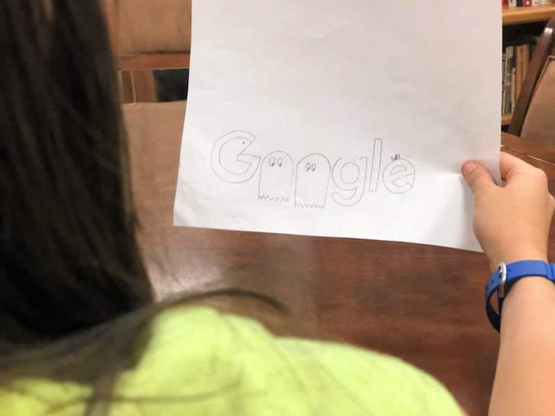 a girl holding her doodle of the word Google