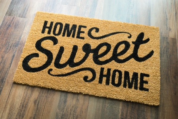a door mat with text reading home sweet home on a wood floor