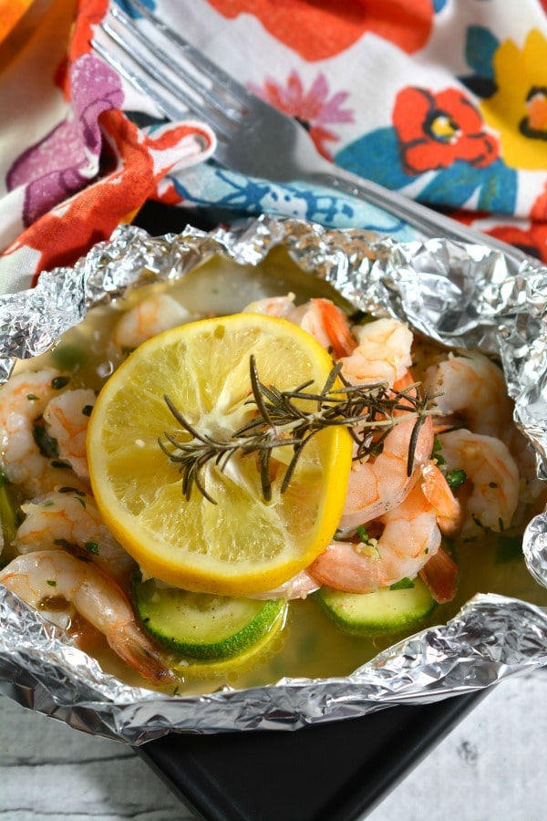 Keto Shrimp Foil Packets topped with a slice of lemon on a floral cloth next to a fork