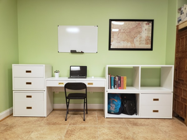 drawers,desk, bookcase, chair, green wall with a whiteboard and a map on it