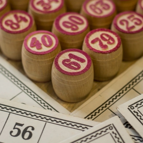 wooden bingo markers with numbers on them and paper bingo cards