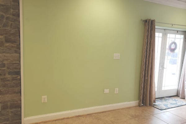 a green wall with a sliding glass door and curtains