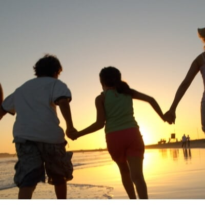family holding hands and running in the ocean water during the sunset