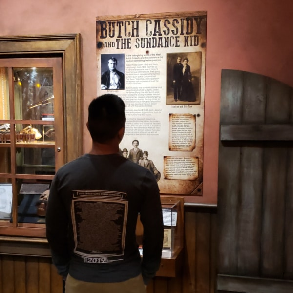 a man looking at a poster with title text reading Butch Cassidy and The Sundance Kid