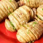Hasselback Potatoes on red plate