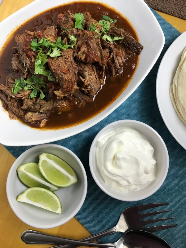 carne guisada in a white dish next to white bowls of sour cream and lime wedges, also a fork and spoon