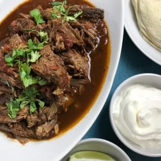 Instant Pot Carne Guisada in white serving dish with side dishes of sour cream and tortillas