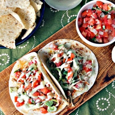 Instant Pot Chicken Enchilada Tacos on serving board with green napkin