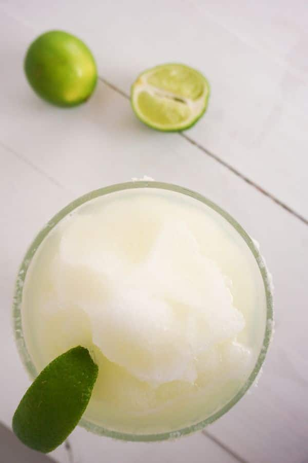 overhead view of a frozen margarita in a glass with a lime wedge in it on a table with limes in the background