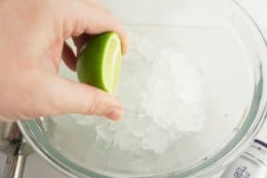 squeezing limes over a glass bowl of ice for a restaurant-style classic frozen margarita