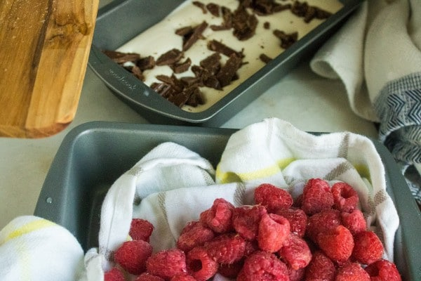a pan of raspberry ice cream mixture next to a pan with dishcloths and raspberries in it
