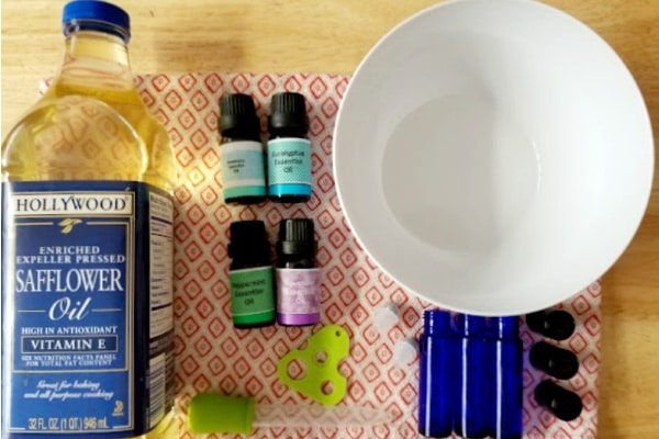 safflower oil, essential oils, a white bowl, a medicine dropper and glass bottles on a linen on a table