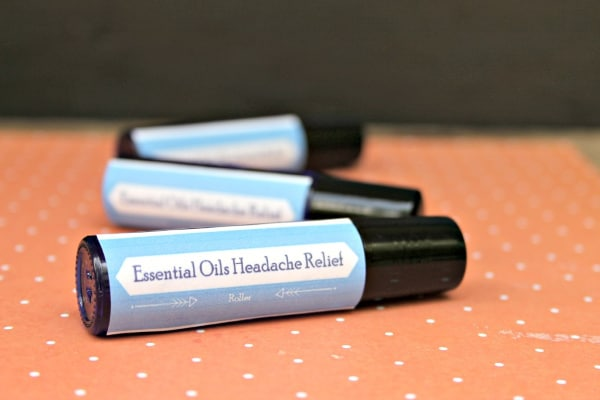 easy essential oil headache relief rollers on an orange and white dotted paper