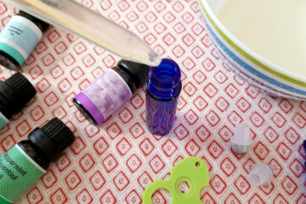 bottles of essential oil, a medicine dropper, and a bowl on a linen
