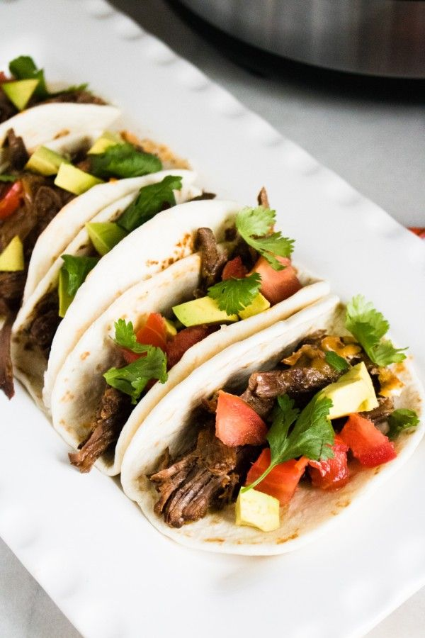 soft tacos on a white platter filled with beef, tomatoes, and parsley