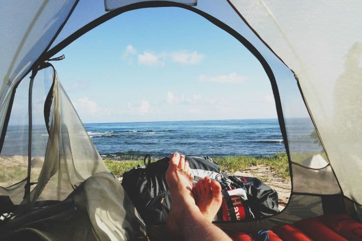 a person's feet laying down in tent facing the water