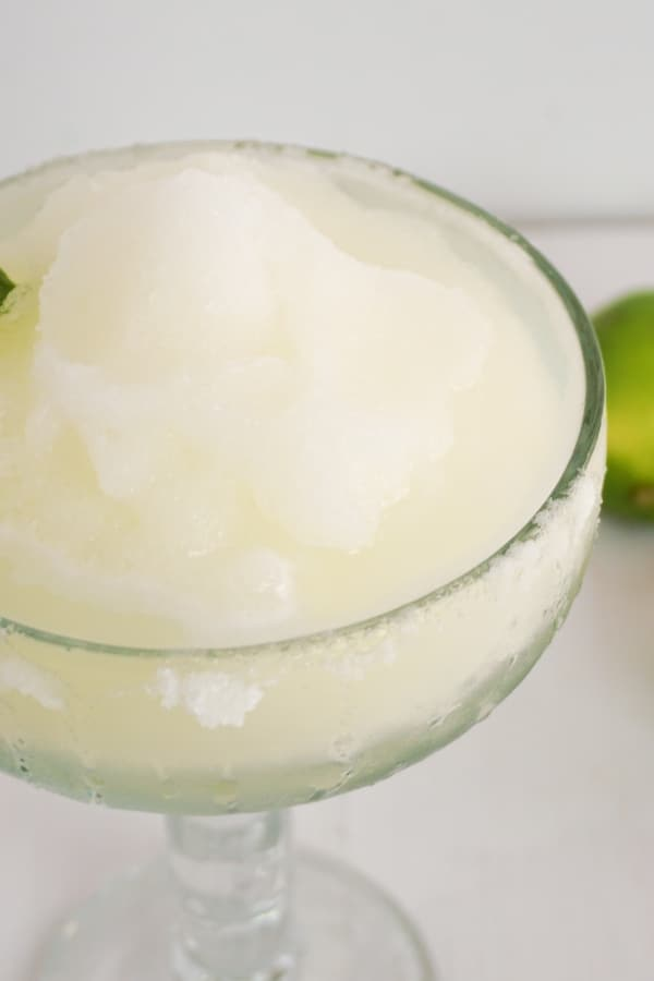 a frozen margarita in a glass on a table with a lime in the background