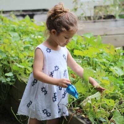 little girl watering her garden