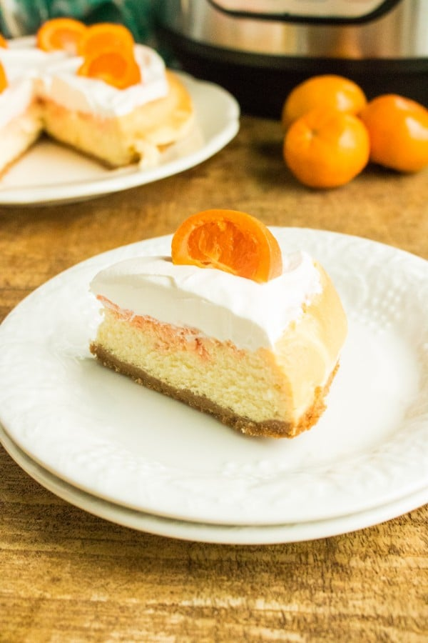 Close up of slice of orange cream cheesecake on white plate with remaining cheesecake, mandarin oranges, and instant pot in background