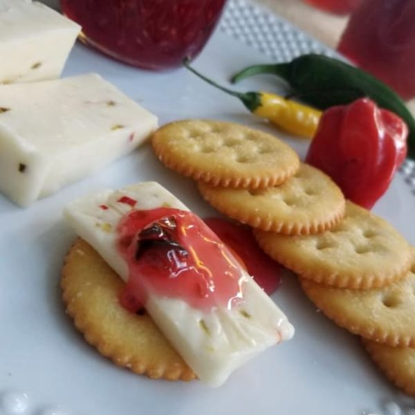 raspberry hot pepper jelly on a slice of cheese on a cracker with more crackers, cheese and peppers on a plate