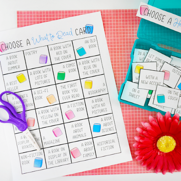 printable summer reading challenge next to a blue plastic box filled with cut up cards from the printable next to a red flower on a red checkered background