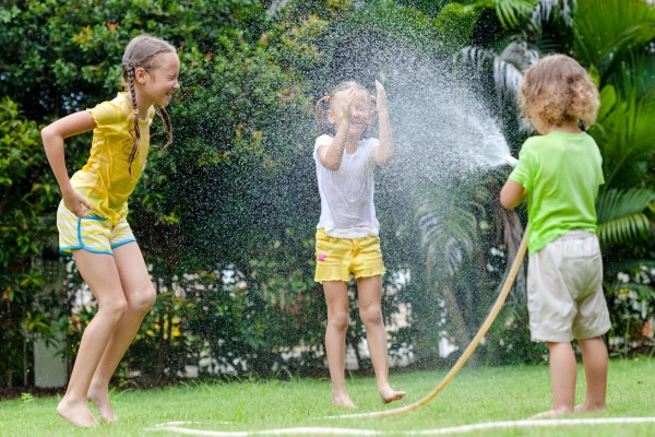 three kids outside with one of them spraying water from a house on the others