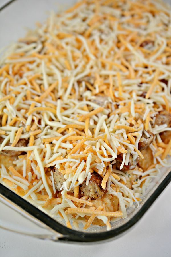 a glass baking dish filled with chicken and tater tots topped with shredded cheese