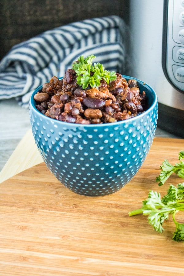 pork and beans topped with parsley in a blue bowl on a wooden table with a blue and white striped cloth and an instant pot in the background