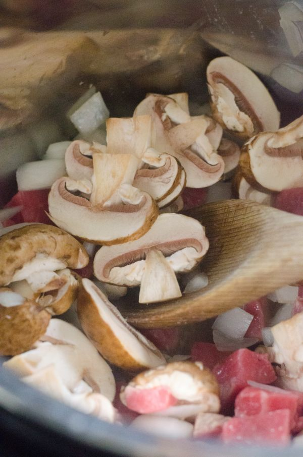 sliced mushrooms, beef and onions in a pot with a wooden spoon