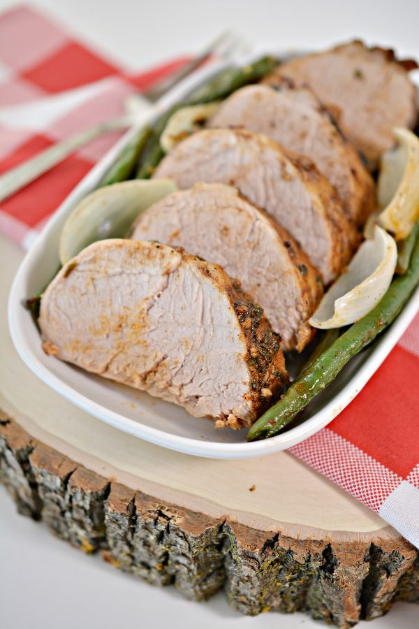 Jamaican Jerk Pork Tenderloin with onions and green beans in a white baking dish on a red linen on a piece of wood