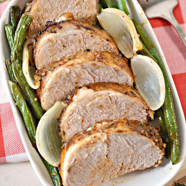 Jamaican Jerk Pork Tenderloin with onions and green beans in a white baking dish on a red linen
