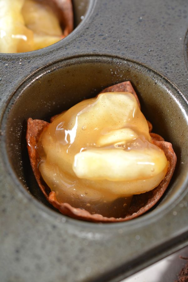 apple pie filling on a wonton wrapper in a muffin tin