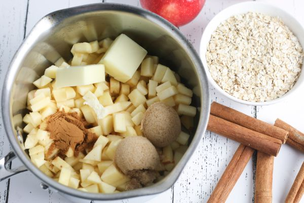 a pan filled with diced apples, butter, brown sugar and cinnamon next to cinnamon sticks, a bowl of oats, and an apple all on a white wood table