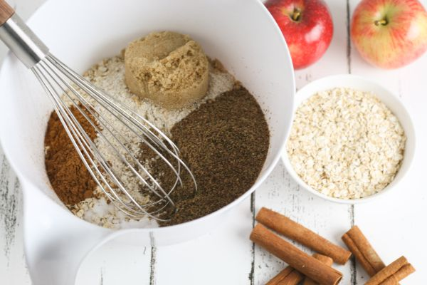 a white bowl filled with oat flour, brown sugar and spices with a whisk in it next to cinnamon sticks, oats and apples all on a white wood table