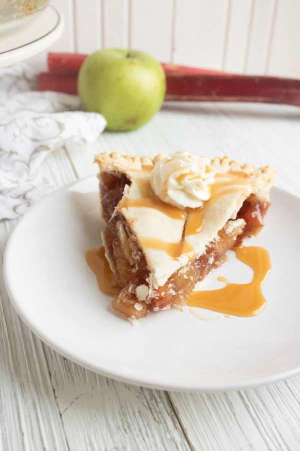 a slice of Apple and Rhubarb Pie on a white plate drizzled with caramel sauce and some whip cream with an apple in the background