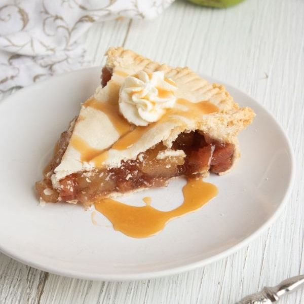 a slice of Apple and Rhubarb Pie drizzled with caramel topped with whip cream on a white plate on a white wood table